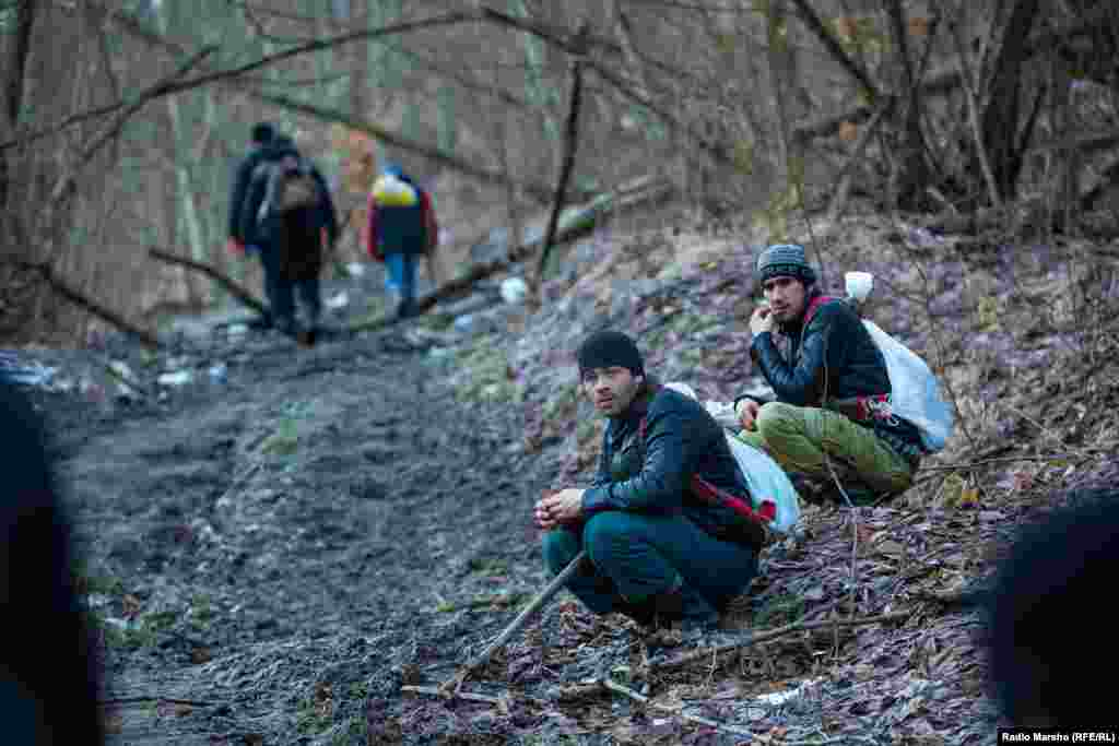 Two men take a break from their work. They use a rake to brush aside the snow and fallen foliage covering the coveted garlic.