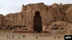 Бамиан провинциясындағы қиратылған Будда мүсінінің орны жанында ауған балалары футбол ойнап жүр.