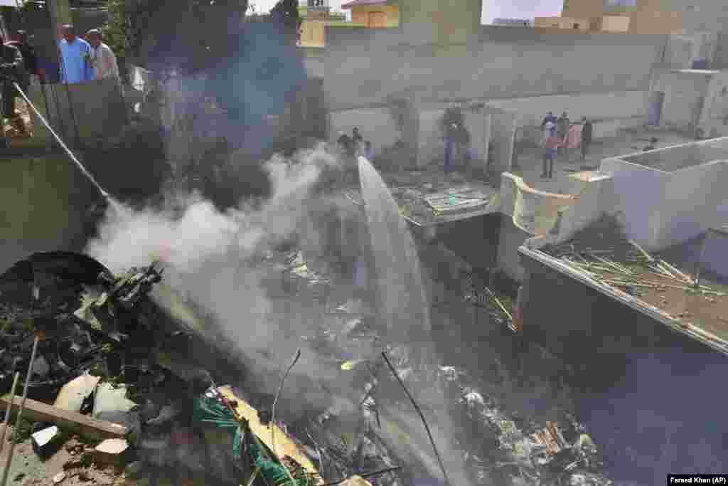 Спасатели тушат пожар, вызванный авиакатастрофой в Карачи (Пакистан) 22 мая 2020 года. В результате трагедии погибли 98 человек
