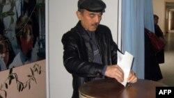 Житель Ташкента бросает бюллетень в урну для голосования. 21 декабря 2014 года.