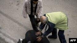Поранений чоловік допомагає іншому в Хомсі після ракетного обстрілу, 11 січня 2011 року