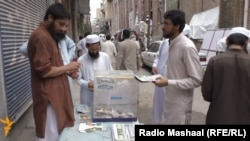 Members of Jammat-ud Dawa selling their newspaper and raising funds in Peshawar.