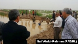 عمّال يفتحون ثغرة لتصريف مياه الأمطار في واسط