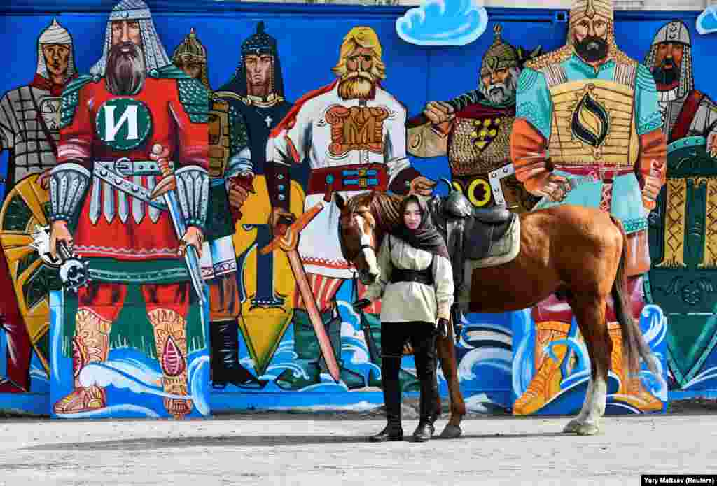 A Russian woman stands with a horse next to graffiti during celebrations of the Defender of the Fatherland Day in Vladivostok on February 23. (Reuters/Yuri Maltsev)