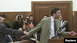Tadašnjeg ministra informisanja Aleksandra Vučića (desno), funkcionera Srpske radikalne stranke, drži za ruku generalni sekretar vladajuće Socijalističke partije Srbije Zoran Anđelković, dok se raspravlja sa predsednikom Skupštine Draganom Tomićem, Beograd (23. oktobar 2000.)