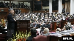Afghan President Hamid Karzai (standing) addresses the Afghan parliament in February 2010.
