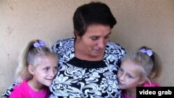 Maria Barbanou (center) is raising two of her granddaughters while their mother, Maria's daughter, is working in Italy.