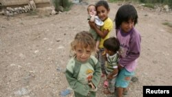 Syrian refugee children, who fled the violence, stand on a road at a northern Lebanese border village