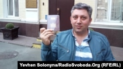 Fikrat Huseynli holds up his Dutch passport outside a Kyiv court on April 16.