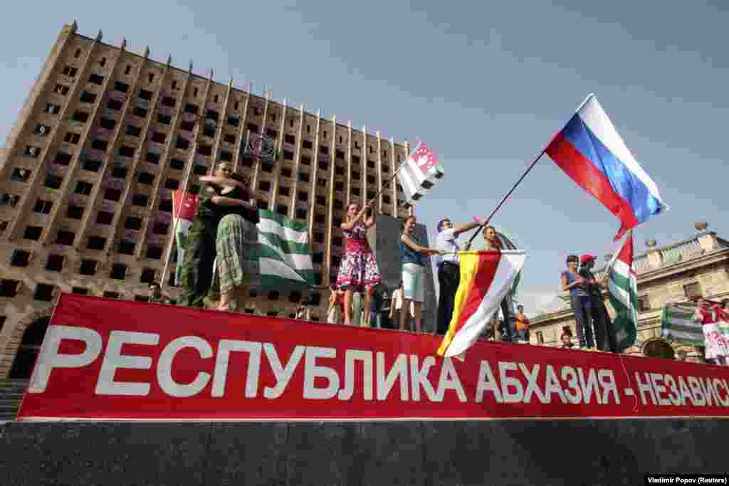 In the first major crisis of Medvedev's presidency, Russia fought a five-day war with Georgia over the breakaway Georgian territories of Abkhazia and South Ossetia. In this photo from August 26, 2008, people in Sukhumi wave flags as they celebrate Moscow's recognition of the territories as independent states.