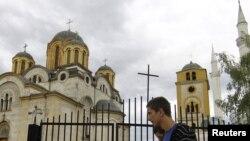 Мужчины идут вдоль улицы, где по соседству друг с другом расположены мечеть и православный храм.