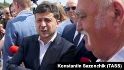 Ukrainian President Volodymyr Zelenskiy (left) talks to local residents in the central city of Cherkasy on July 31.