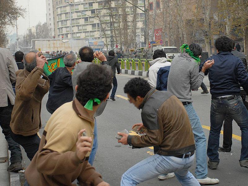 Eýranly protestçiler Tähranda polisiýa daş zyňýarlar. 27 dekabr. 2009