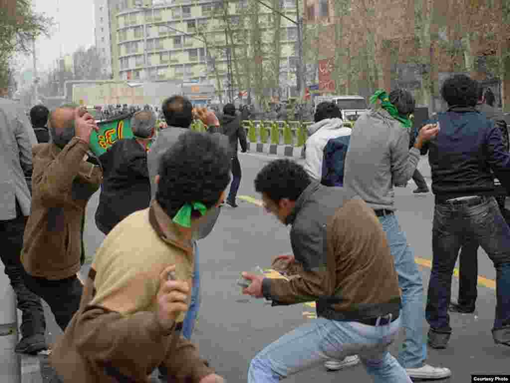 Iran -- Iranian opposition supporters throw stones towards riot policemen during clashes in Tehran, 27Dec2009 - Photo by Sara (Use only with Photographer's name