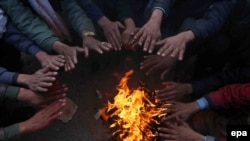 FILE: Afghan people gather around a fire to beat the cold as winter season approaches.