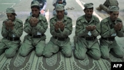 Cadets from the Afghan Local Police pray at the police academy on the outskirts of Jalalabad on June 20.