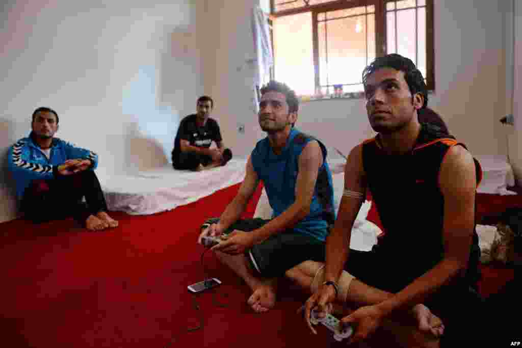 Afghan footballers play a video game in a dorm room while others watch at their communal house in Kabul.