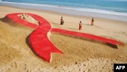 Халықаралық СПИД-пен күрес күні (1 желтоқсан) қарсаңында құмнан жасалған 100 метрлік СПИД-пен күрес белгісі. Үндістан, 30 қараша 2012 жыл.