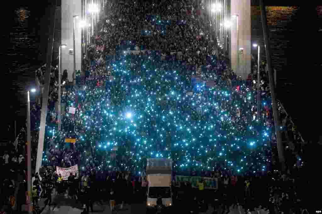 People hold up their mobile phones as they protest against a new tax on Internet data transfers in the center of Budapest. (epa/Janos Marjai)