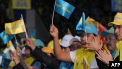 Люди размахивают флажками на форуме партии «Нур Отан».