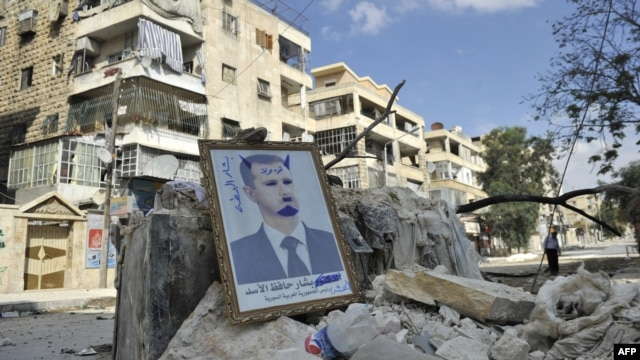Syria -- A portrait of President Bashar al-Assad defaced to look like a devil is placed on rubble along a street during clashes with government forces in a Saif al-Dawla district of the northern city of Aleppo, 09oct2012