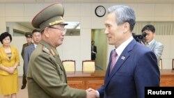 Cоветник по национальной безопасности Южной Кореи Ким Кван Чжин (справа) пожимает руку Хван Пьонг Со (слева), высшему военному советнику северокорейского лидера Ким Чен Ына