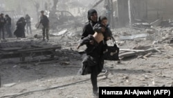 A Syrian woman holds a child and runs for cover following government air strikes on the rebel-held enclave of Douma late last month.