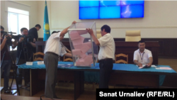 Члены избирательной комиссии выкладывают бюллетени для подсчета голосов. Уральск, 7 августа 2017 года.