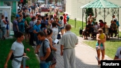 People gather outside an office of the Russian federal migration service.
