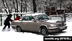A motorist tries to get a car moving in Tashkent earlier this month.