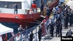 Migrants leave a ferry anchored at port in the Turkish coastal town of Dikili on April 4.