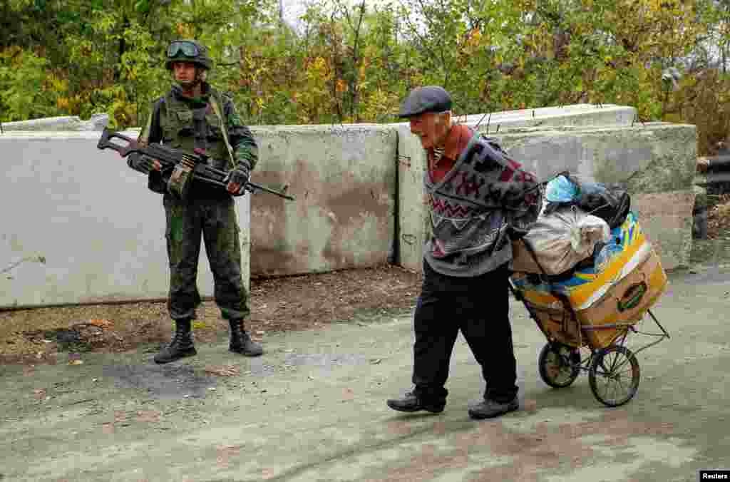 A man carries his belongings past a Russia-backed separatist in the settlement of Stanytsia Luhanska in the Luhansk region of eastern Ukraine. (Reuters/Alexander Ermochenko)