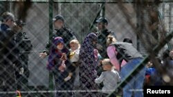 Police officers guard women and children who are relatives of Kosovo Jihadists who returned from Syria, at foreigners detention centre in Pristina, Kosovo, April 20, 2019. REUTERS/Laura Hasani
