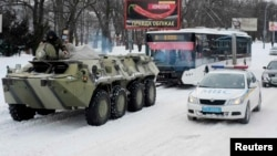 A Ukrainian armored personnel carrier tows a trolleybus behind it on a road covered with snow in Kyiv. (file photo)