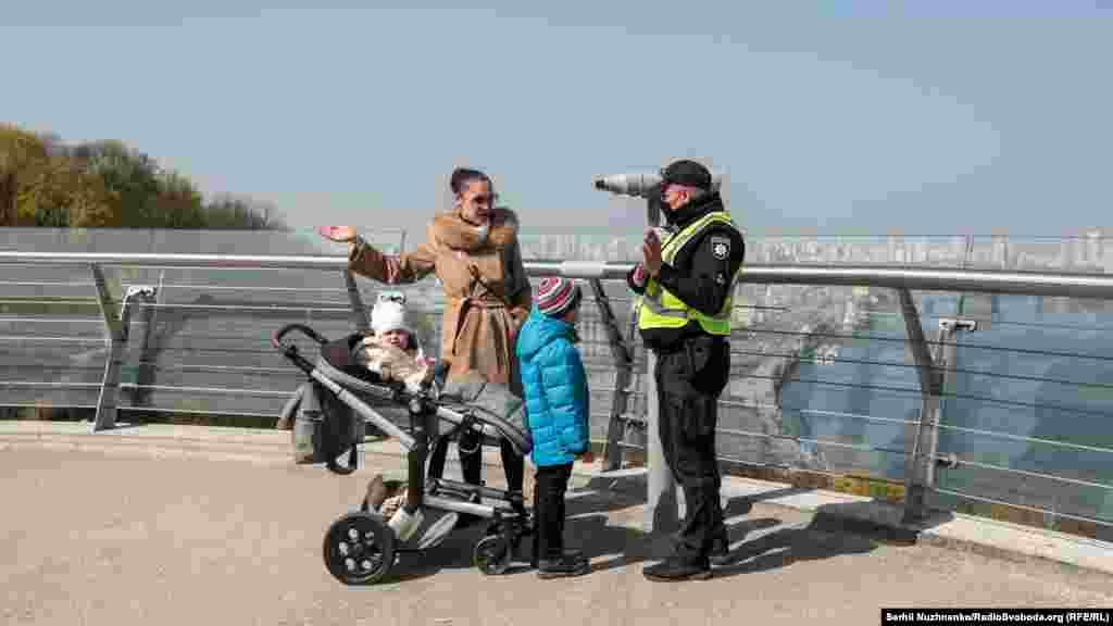 Працівники поліції патрулюють Пішохідно-велосипедний міст через Володимирський узвіз і в разі необхідності вдаються до усних попереджень громадян, які порушують постанову Кабінету міністрів України (КМУ). Київ, 7 квітня 2020 року
