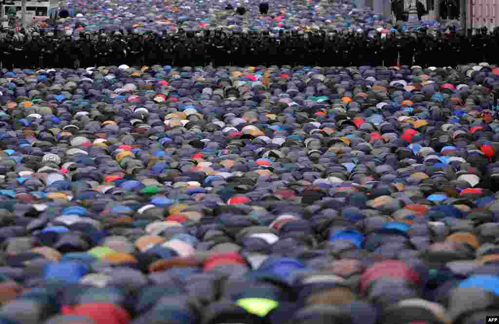 Police stand guard as Muslims pray in a street near the Central Mosque during the Eid al-Adha festival in Moscow. (AFP/Vasily Maximov)