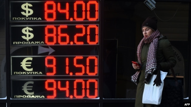 A woman walks past a board listing foreign currency rates against the Russian ruble in Moscow on January 21.