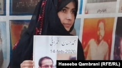 Haseeba Qambrani holds the photo of her disappeared brother Hassan Qambrani at a sit-in protest in Quetta, Balochistan.
