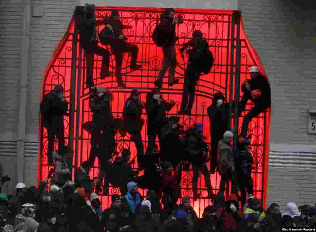 Люди на воротах біля будівлі адміністрації президента під час мітингу прихильників інтеграції в ЄС у Києві, 1 грудня 2013