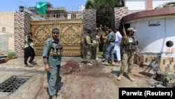 FILE: Afghan security force stand at the site of an attack in Jalalabad.