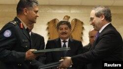Pas nënshkrimit të marrëveshjes, zëvendësministri i Jashtëm sirian Faisal al-Mikdad (djathtas) dhe gjenerali Abhixhit Guha(majtas) nga Departamenti për Operacione Paqeruajtëse i OKB-së, 19 prill, 2012