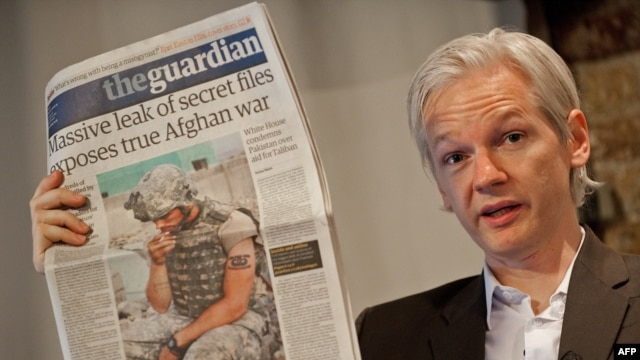 "The Australian founder of the whistle-blowing website WikiLeaks, Julian Assange, holds up a copy of ""The Guardian"" at a press conference in London on July 26."