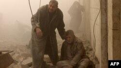 رجل يساعد جريحاً في قصف جوي على منطقة بمدينة حلب السورية