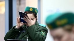 Belarus -- A Belarusian border guard checks a passenger's passport with magnifying glass in a train after it arrived from Lithuania, at the railway station Gudogai, November 22, 2016