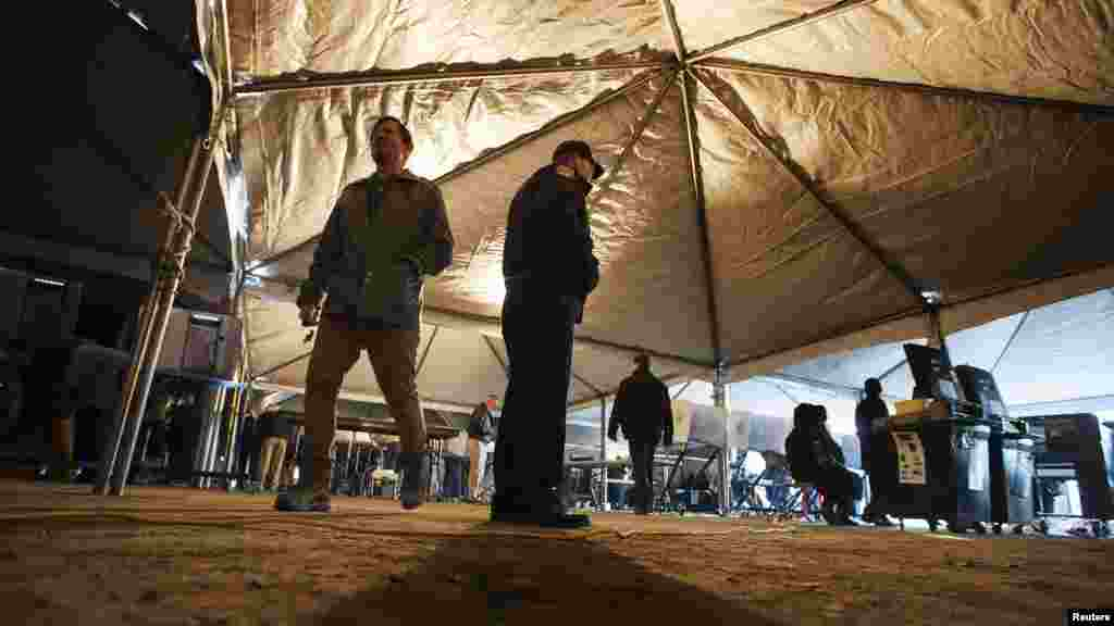 A voter walks past a New York police officer inside a tent at a polling site built to service residents of the Queens borough neighborhoods of Breezy Point and the Rockaways, whose original site was devastated by superstorm Sandy.
