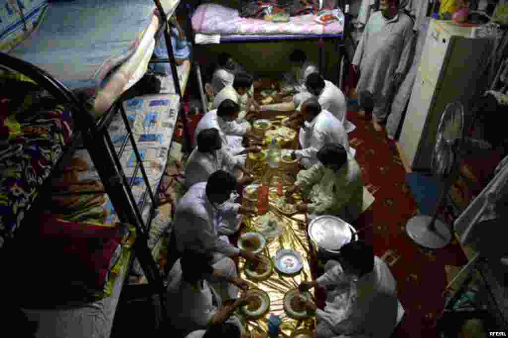 Migrant workers share an evening meal in their temporary home.