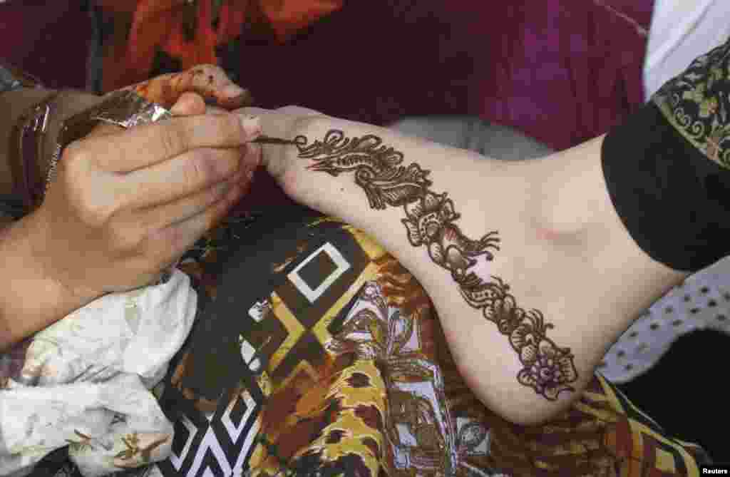 A beautician paints henna on the foot of a woman at a market stall in Karachi, Pakistan.