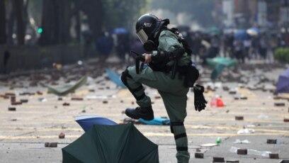 Pripadnik interventne policije gazi kišobran kojeg su koristili demonstranti tokom prodemokratskih protesta ispred univerziteta u Hong Kongu, novembar 2019.