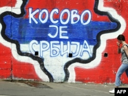 """A map of Kosovo painted on a wall with the words """"Kosovo is Serbia"""" in Belgrade."""