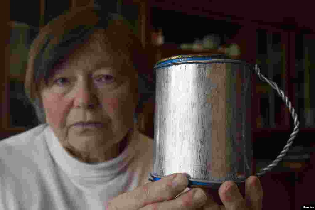 Zinaida Tarasevich, 76, holds a self-made tin mug that her mother gave her before she died. This mug was in remembrance of the primitive kitchen utensils her parents had to use during their long years in a concentration camp in the Russian Arctic. Of the more than 20 relatives sent to the camp as political prisoners, only her mother and father managed to survive and return home to Minsk after Stalin's death.